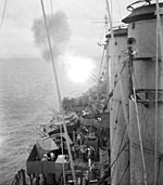 The cruiser HMAS Shropshire bombarding Japanese positions at Balikpapan, Borneo, on 30 June 1945