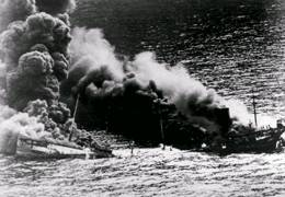 Broken in two by a torpedo, this tanker sinks beneath the waves. Torpedoes with magnetic pistols exploded beneath the target, breaking the hull in two