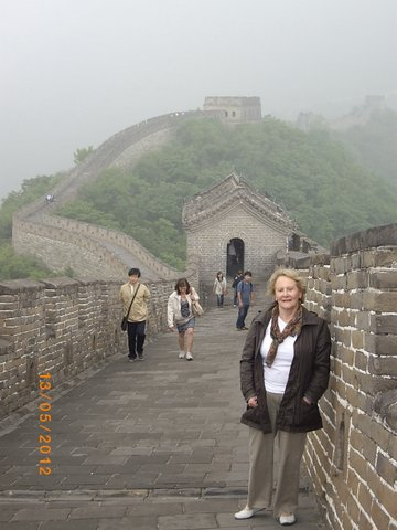 Denise on the Wall at Bejing, with the wall stretching into the distance
